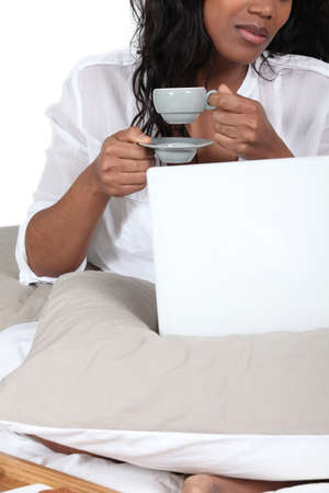 African woman drinking her coffee in bed photo