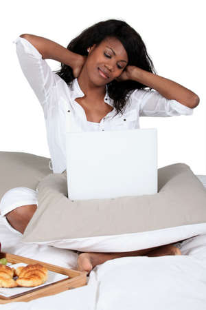 breakfasting: black woman cross-legged on bed with laptop