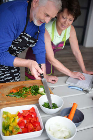 Senior couple preparing a meal searching for a recipe on internet Stock Photo - 17479794