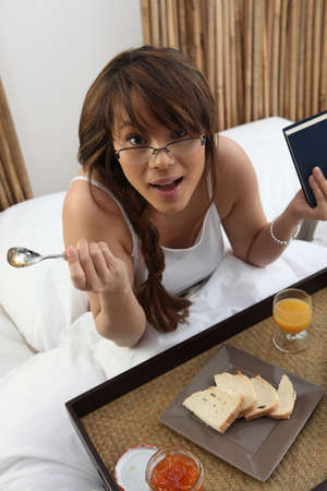 Surprised young woman having breakfast in bed photo