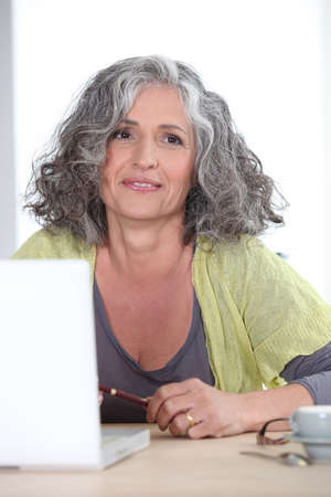 Gray-haired woman in front of laptop computer photo