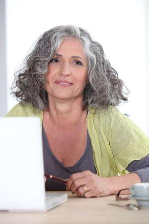 mujeres ancianas: Mujer de pelo gris en frente de la computadora port�til