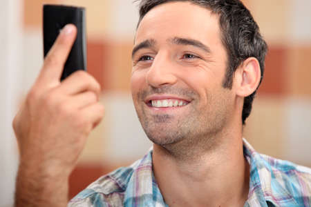 smile close up: Man looking at phone smiling Stock Photo