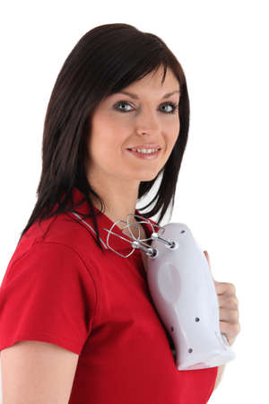 Brunette holding electric whisk photo