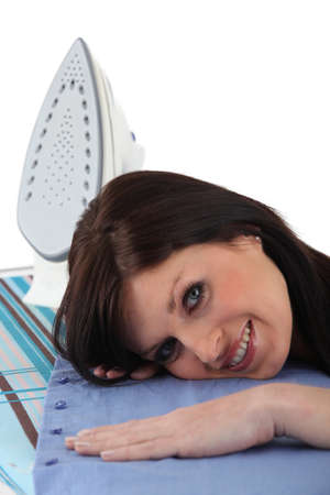smoothen: Woman laying her head on an ironing board