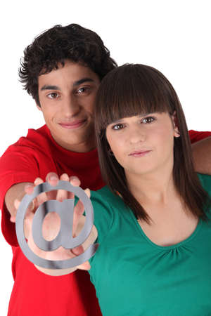 Couple holding an at symbol photo