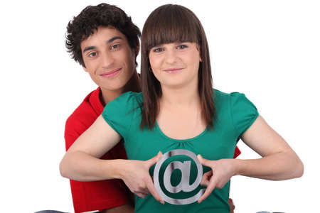 two teenagers embracing and holding an at sign photo