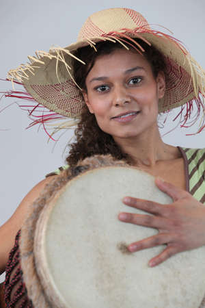 Woman wearing a straw hat and playing the djembe photo