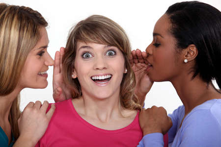 chatter: Two women whispering into friends ear Stock Photo