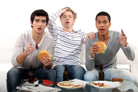 davenport: male trio watching soccer match on TV and eating hamburgers Stock Photo