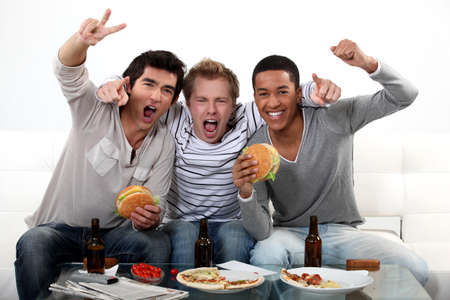 watching football: three friends eating while watching television