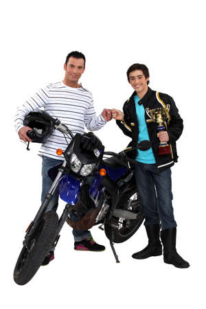 Men with motorbike and gold cup photo