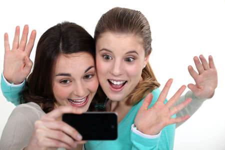 Two girls posing with camera phone photo