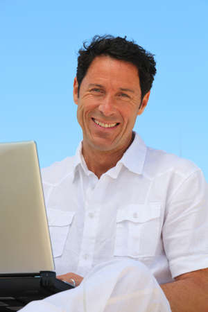 40 45: Man smiling on laptop in blue sky