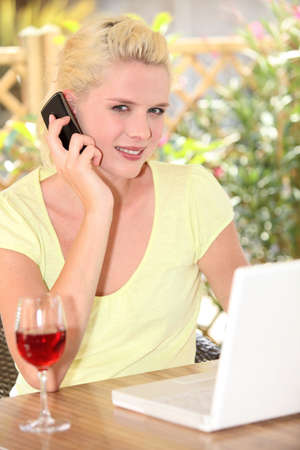 Woman talking on her mobile phone in front of her laptop and a glass of wine photo
