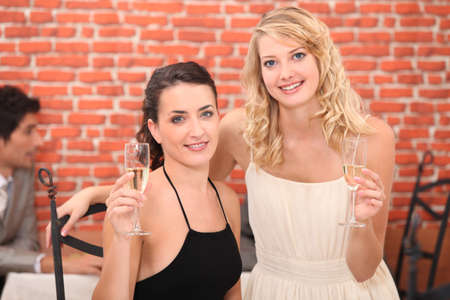 two girlfriends drinking champagne photo