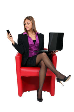 high flier: Woman sat with mobile telephone and computer Stock Photo