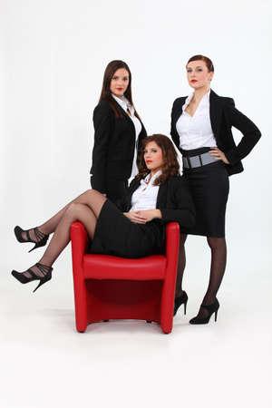 Three confident businesswomen stood by chair photo