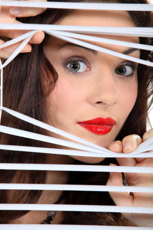 think through: woman looking through window blinds