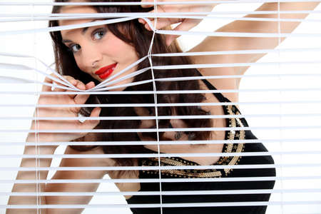 cheeky: Brunette looking through blinds Stock Photo
