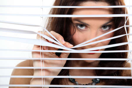 A cute brunette spying through the blinds  photo