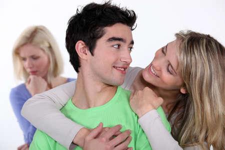 celos: Pareja de enamorados haciendo caso omiso de su amigo