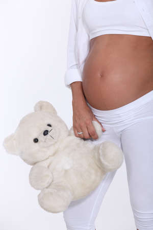 Pregnant woman holding teddy bear photo
