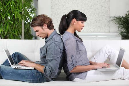 personas abrazadas: Pareja con dos computadoras portátiles en el sofá Foto de archivo