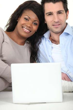 couple mixte: Couple mixte assis avec ordinateur portable Banque d'images