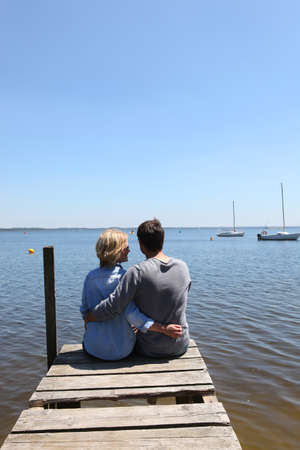 Couple sitting on the end of a pontoon with their arms around each other photo