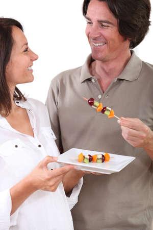 fruit skewers: Pareja de comer brochetas de fruta Foto de archivo