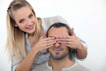 hands covering eyes: Young woman covering her husband Stock Photo