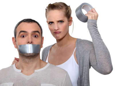 Woman taping boyfriends mouth closed photo