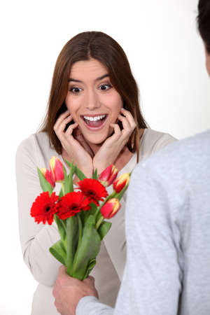 Surprised woman receiving flowers from her boyfriend photo