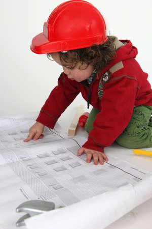 Little boy builder reading newspaper