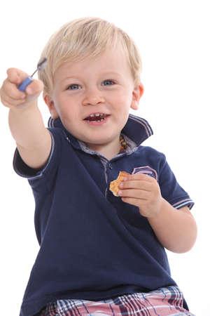 12 18 months: Toddler eating a biscuit and playing with mummy Stock Photo