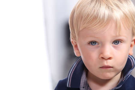 subdued: Landscape portrait of a serious little boy with blonde hair and blue eyes