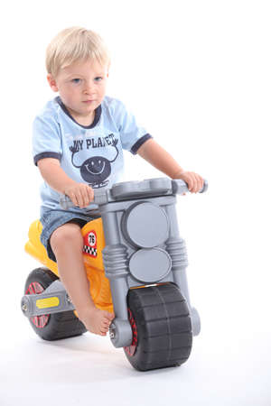little boy on a toy motorcycle photo