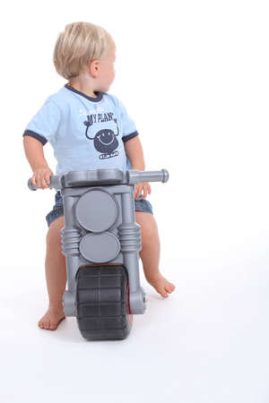 make belief: Child on a toy motorcycle