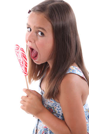 mouth close up: Girl eating heart lolly pop