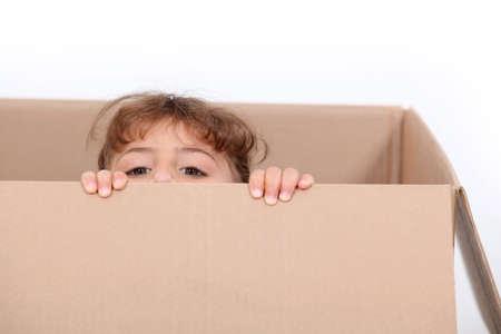 little girl hiding in a cardboard photo