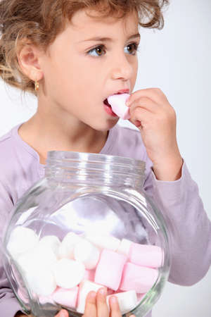 eyes hazel: Cute little girl eating marshmallows Stock Photo