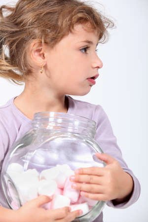 sideway: Little girl holding a jar full of marshmallows  Stock Photo