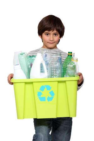 reciclaje de papel: kid holding bañera llena de reciclaje de botellas de plástico vacías Foto de archivo