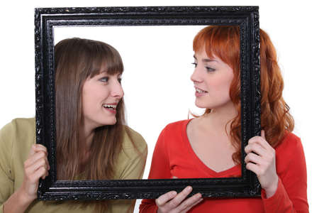 poking: Two women poking heads though empty picture frame Stock Photo