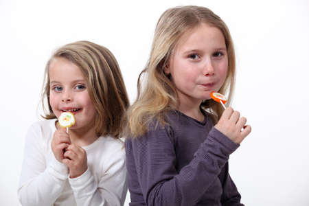 Little girls eating candy photo