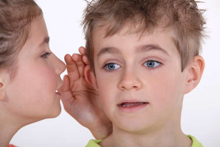 Young girl whispering into a boy photo