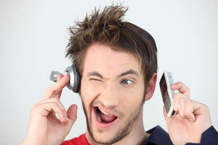 Man holding headphones and mobile telephone photo