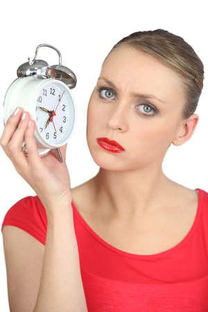 molesto: Grave mujer rubia con aspecto de reloj de alarma