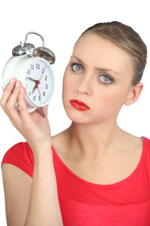 annoying: Serious looking blond woman holding alarm clock